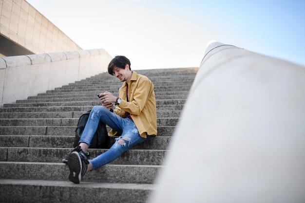 스마트폰을 사용 하 여 도시 야외 계단에 앉아 젊은 남자의 초상화.