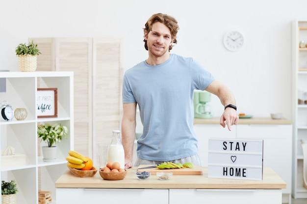 Портрет молодого человека, улыбаясь и указывая на плакат с текстом во время приготовления пищи на кухне
