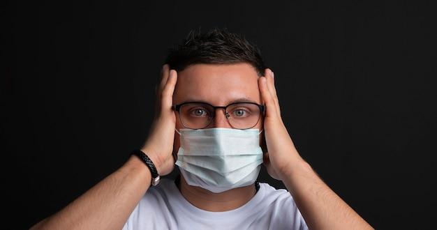 若い男の肖像画は、医療インフルエンザマスクを脱ぐ