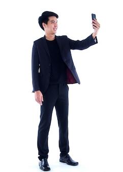 白の上に立っている間彼のスマートフォンでselfieを取る若い男の肖像画