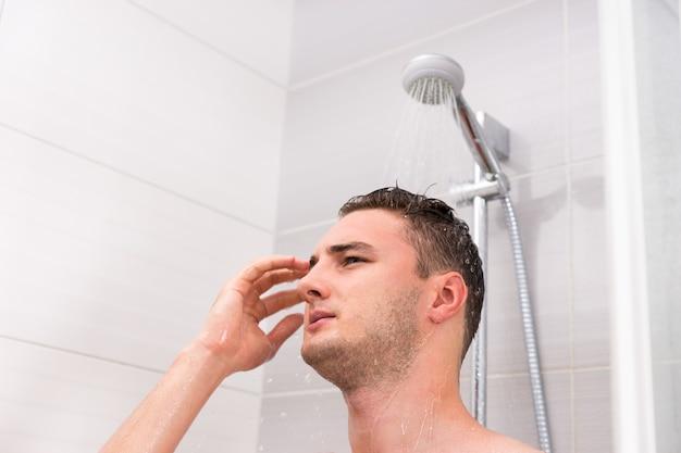 Портрет молодого человека, принимающего душ, стоящего под проточной водой в душевой кабине в современной кафельной ванной комнате