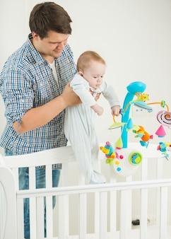 침대에서 그의 9 개월 된 아기 아들을 데리고 젊은 남자의 초상화