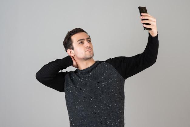 Портрет молодого человека, делающего селфи на серой стене