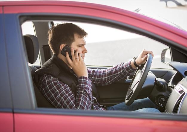 차를 운전하는 동안 전화로 얘기하는 젊은 남자의 초상화