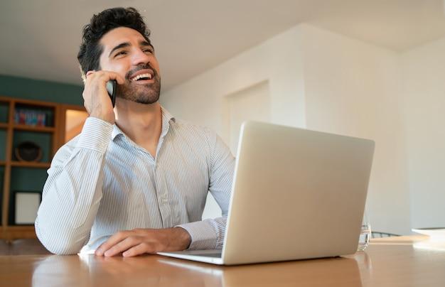 그의 휴대 전화에 얘기 하 고 노트북으로 가정에서 일하는 젊은 남자의 초상화. 홈 오피스 개념