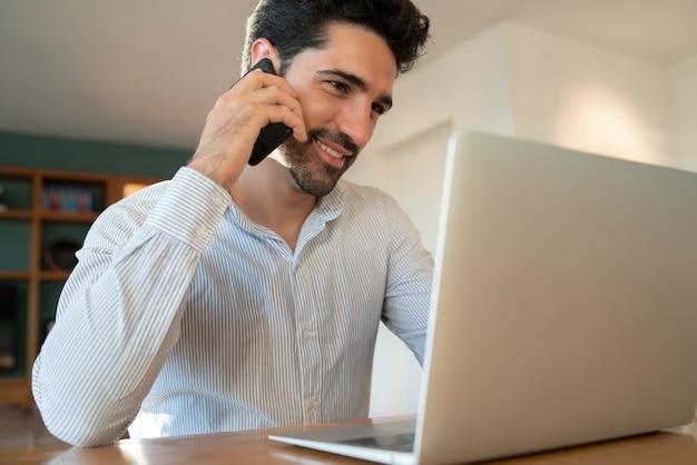 彼の携帯電話で話し、ラップトップで自宅で仕事をしている若い男の肖像画。ホームオフィスのコンセプト。