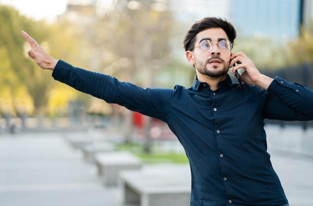 通りの屋外に立っている間、電話で話し、タクシーを呼ぶ若い男の肖像画。