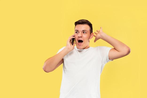 Портрет молодого человека разговаривает по телефону, изолированного на желтой стене