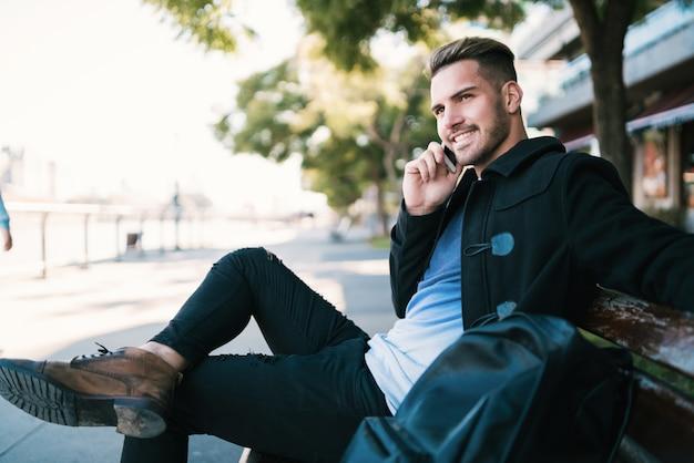 通りの屋外のベンチに座って電話で話している若い男の肖像画。コミュニケーションの概念。