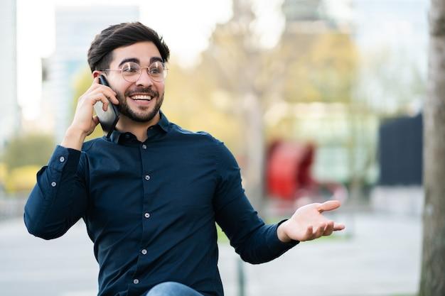 屋外のベンチに座って電話で話している若い男の肖像画。アーバンコンセプト。