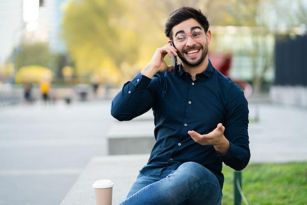 야외 벤치에 앉아있는 동안 전화 통화하는 젊은 남자의 초상화. 도시 개념.