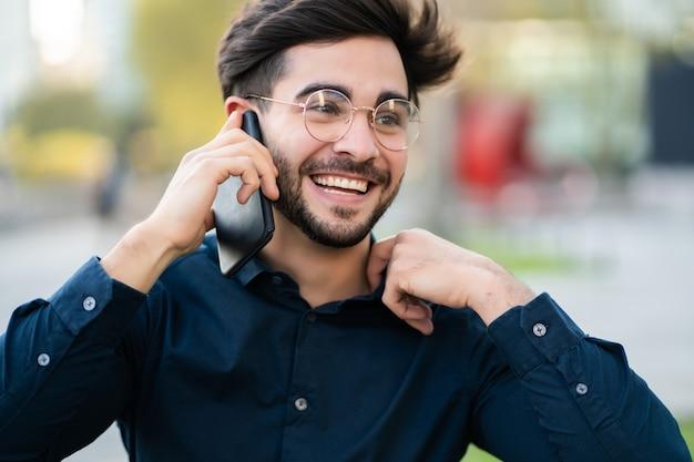 通りで屋外に立っている間、電話で話している若い男の肖像画。アーバンコンセプト。