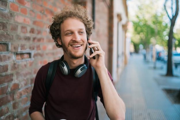 通りで屋外を歩きながら電話で話している若い男の肖像画。コミュニケーションと都市のコンセプト。