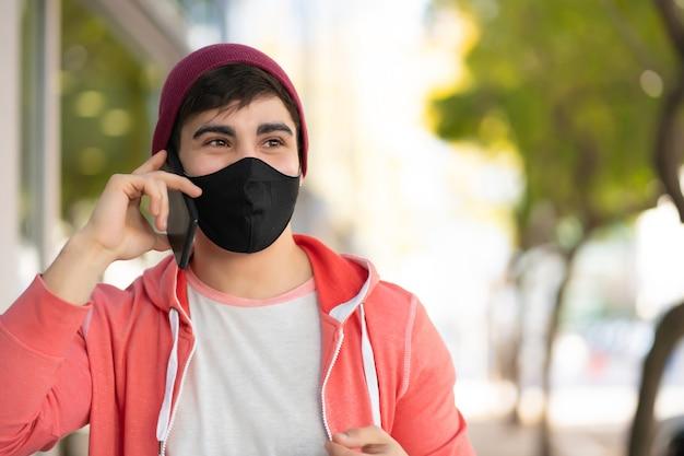 거리에 야외에서 걷는 동안 전화 통화하는 젊은 남자의 초상화. 얼굴 마스크를 착용하는 남자. 도시 개념.