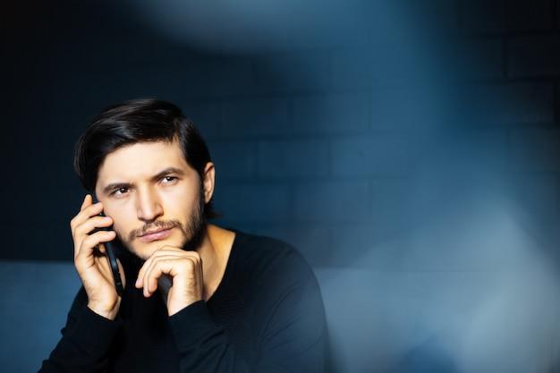 スマートフォンで話している若い男の肖像画。黒レンガの壁の背景。コピースペースの概念。