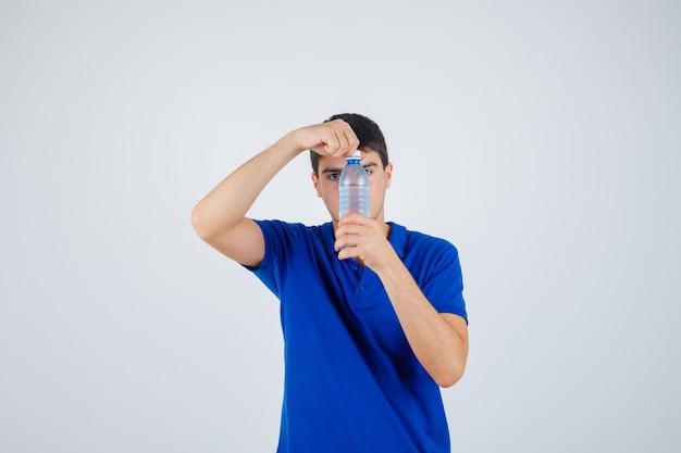 Портрет молодого человека, пытающегося открыть пластиковую бутылку в футболке и внимательно смотрящего на вид спереди
