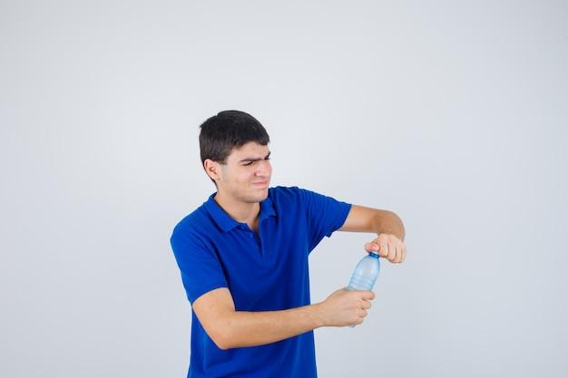 Портрет молодого человека, пытающегося открыть пластиковую бутылку в футболке