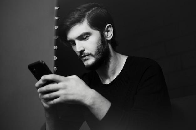 スマートフォンで入力する若い男の肖像画。黒と白の写真。