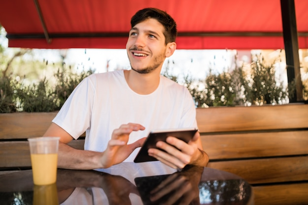커피 숍에 앉아있는 동안 디지털 태블릿을 사용하는 젊은 남자의 초상화. 기술 및 라이프 스타일 개념.