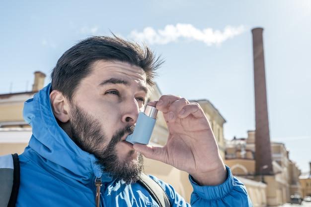 屋外の喘息吸入器を使用して若い男の肖像