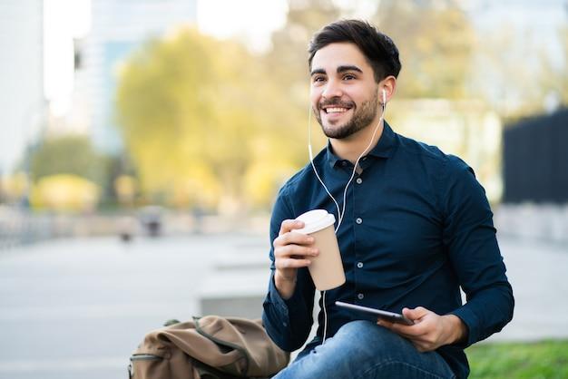 デジタルタブレットを使用して、屋外のベンチに座っている間コーヒーを保持している若い男の肖像画。アーバンコンセプト。