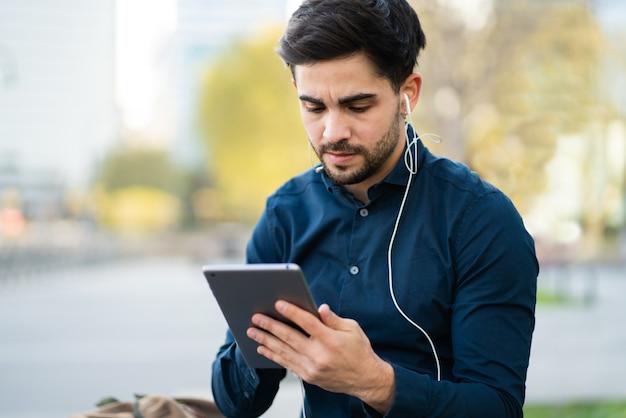 屋外のベンチに座ってデジタルタブレットを使用して若い男の肖像画。アーバンコンセプト。