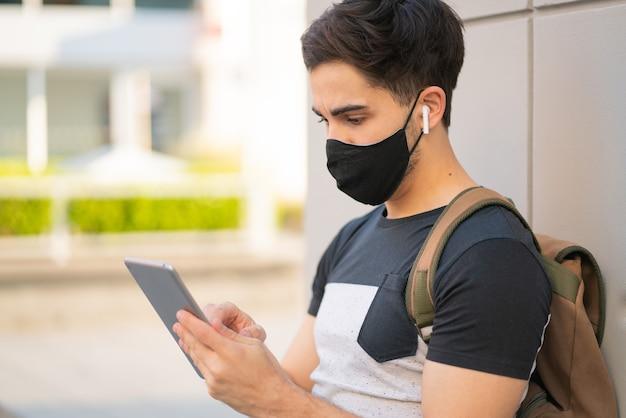 야외에서 서있는 동안 디지털 태블릿을 사용하는 젊은 남자의 초상화