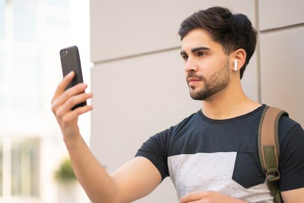 야외에서 서있는 동안 휴대 전화의 잠금을 해제하기 위해 얼굴 id를 사용하는 젊은 남자의 초상화.