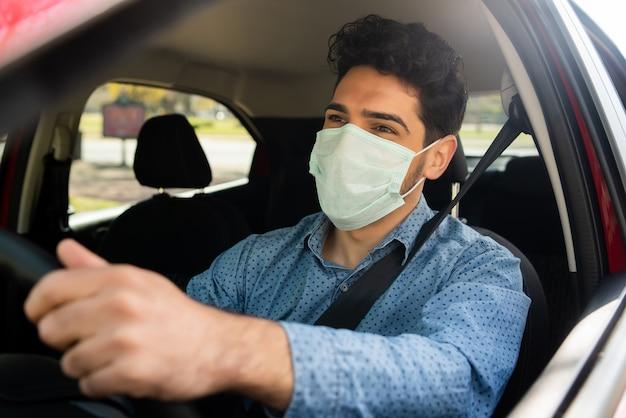 출근 길에 그의 차를 운전하는 동안 얼굴 마스크를 사용하는 젊은 남자의 초상화. 전송 개념. 새로운 정상적인 라이프 스타일 개념.
