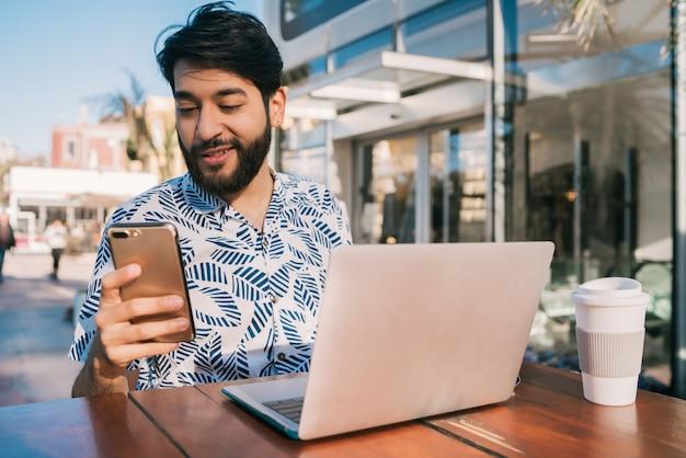Портрет молодого человека, использующего свой ноутбук и использующего свой мобильный телефон, сидя в кафе.