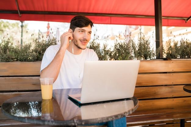 コーヒーショップに座っている間彼のラップトップを使用して若い男の肖像画。技術とライフスタイルのコンセプト。