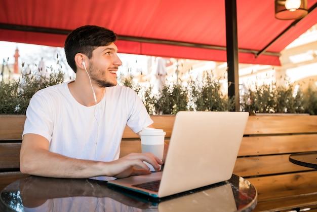 コーヒーショップに座っているときに彼のラップトップを使用して若い男の肖像画。テクノロジーとライフスタイルのコンセプト。