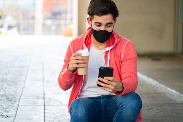 Портрет молодого человека, использующего свой мобильный телефон и пить кофе, сидя на открытом воздухе на улице. человек в маске для лица. городская концепция.