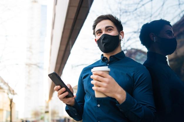 彼の携帯電話を使用して、通りで屋外に立っている間コーヒーを保持している若い男の肖像画。新しい通常のライフスタイルのコンセプト。アーバンコンセプト。