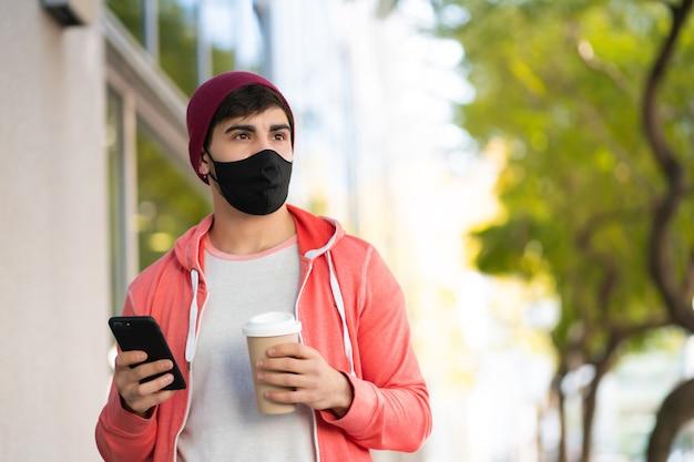 Портрет молодого человека, использующего свой мобильный телефон и держащего чашку кофе во время прогулки по улице. человек в маске для лица. городская концепция.