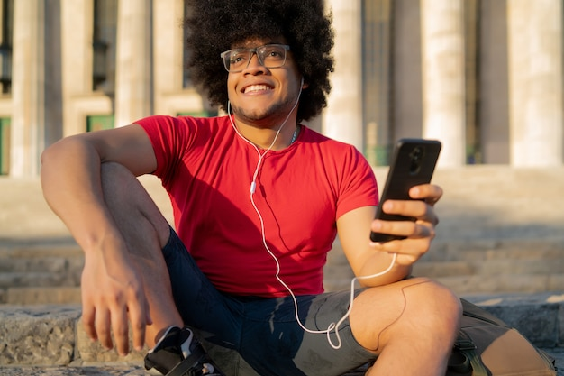 彼の携帯電話を使用して、屋外に座っている間スケートローラーを身に着けている若い男の肖像画