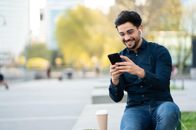 屋外のベンチに座っているときに彼の携帯電話を使用して若い男の肖像画。アーバンコンセプト。