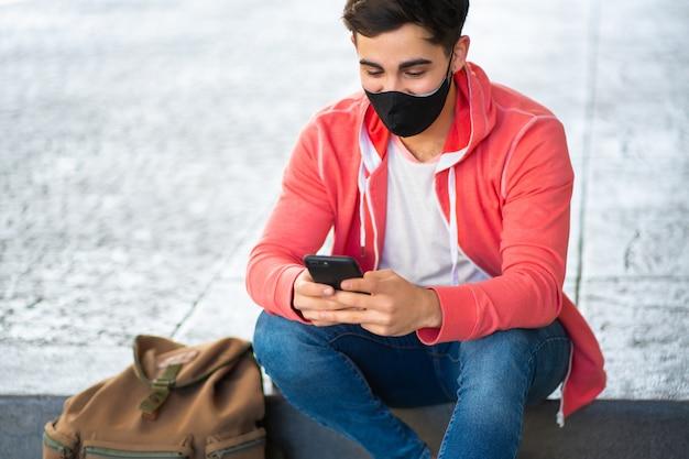야외에서 거리에 앉아있는 동안 그의 휴대 전화를 사용하는 젊은 남자의 초상화. 얼굴 마스크를 착용하는 남자. 도시 개념.