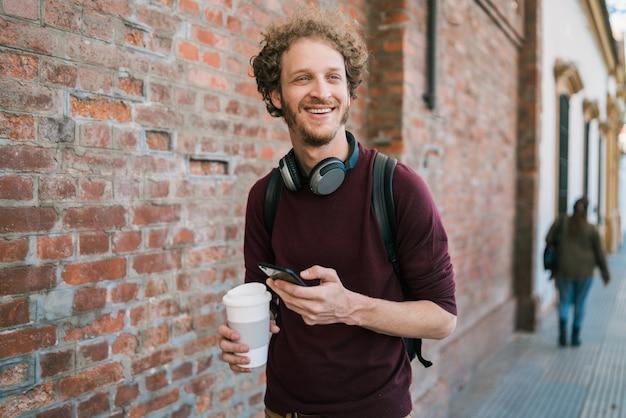 通りを屋外で歩きながら彼の携帯電話を使用して若い男の肖像画
