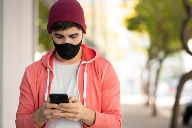 거리에 야외에서 걷는 동안 자신의 휴대 전화를 사용하는 젊은 남자의 초상화. 얼굴 마스크를 착용하는 남자. 도시 개념.