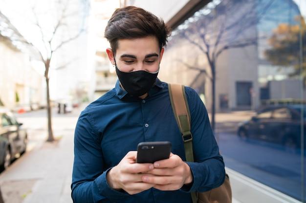 거리에 야외에서 걷는 동안 자신의 휴대 전화를 사용하는 젊은 남자의 초상화. 새로운 정상적인 라이프 스타일 개념. 도시 개념.