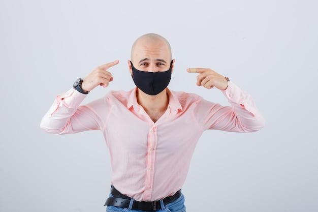 보호 마스크를 착용하고 자신을 가리키는 젊은 남자의 초상화