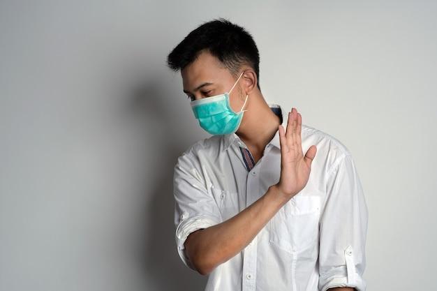 Портрет молодого человека в маске здоровья, показывающий жест отказа