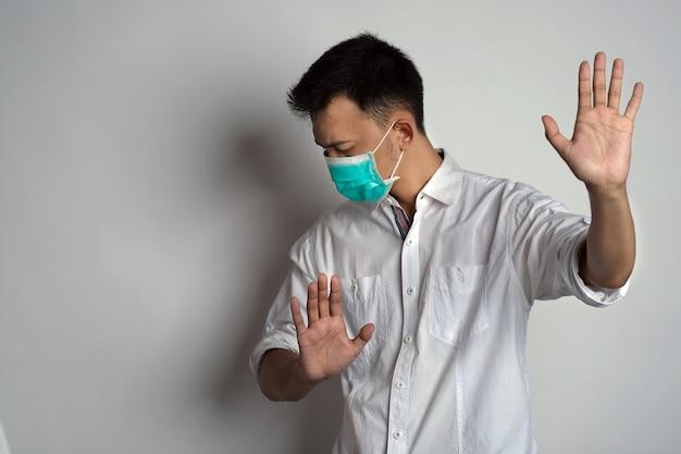 Портрет молодого человека в маске здоровья, стоящего с лицом, повернутым вправо и демонстрирующего отказ
