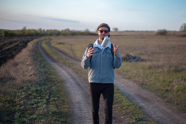 手に再利用可能なアルミニウム熱水ボトルを保持しているバックパックを持つ若い男の肖像画