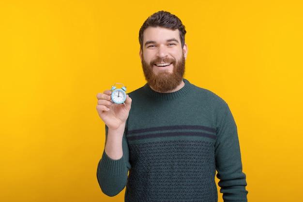 小さな目覚まし時計を保持しているひげを持つ若い男の肖像