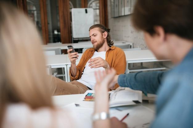 금발 머리와 수염을 가진 젊은 남자의 초상화는 테이블에 그의 다리를 던져 교실에서 핸드폰을 사용하여