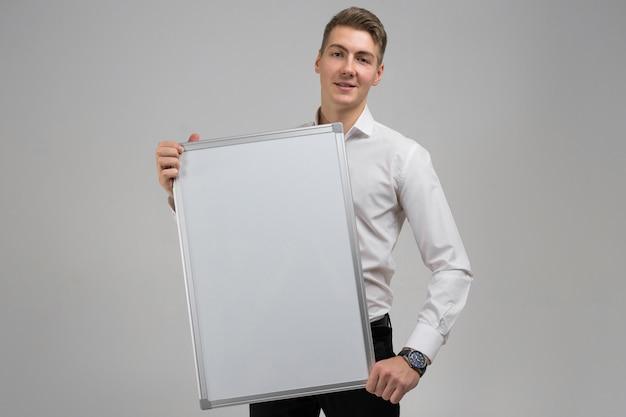 分離された彼の手できれいな磁気ボードを持つ若い男の肖像