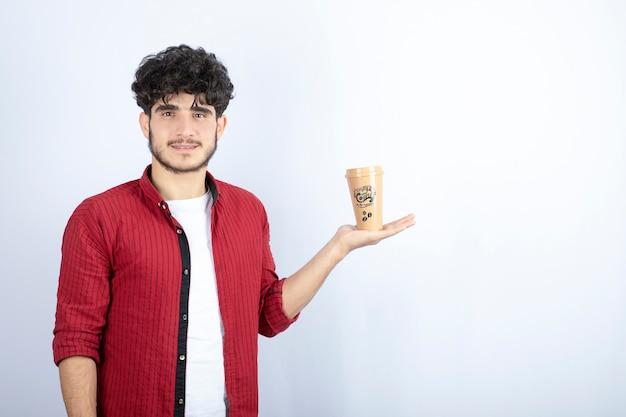 흰색 바탕에 서있는 커피 한잔과 함께 젊은 남자의 초상화. 고품질 사진