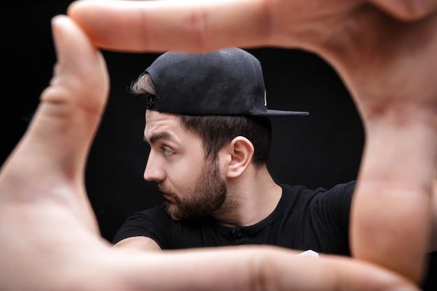 Портрет молодого человека с темными волосами в рубашке и шляпе на черном фоне укомплектовывает кадром руки